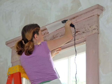 Flaking paint is re-adhered with tacking iron to prevent further paint loss